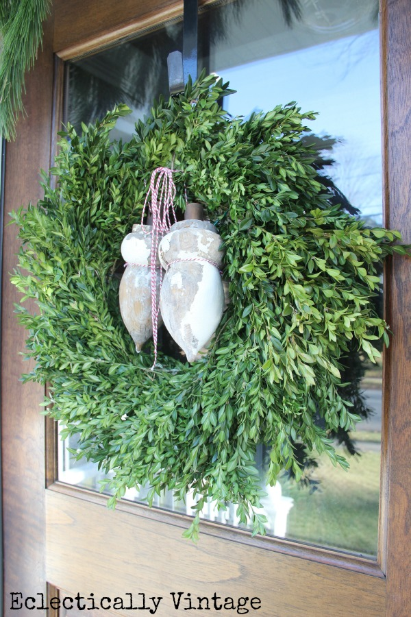 Love a classic boxwood wreath for Christmas and the antique finials add the perfect touch kellyelko.com