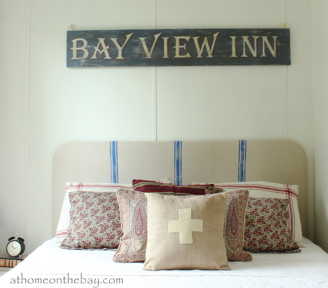 Cottage tour filled with fabulous decorating ideas like this DIY French Grainsack Headboard!