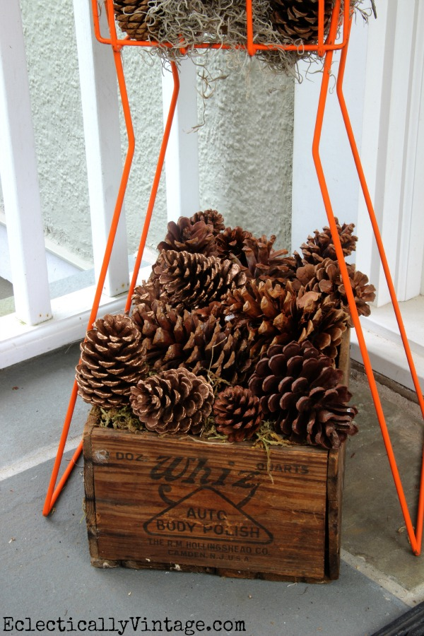 Pinecones in a vintage crate - see more of this fall porch kellyelko.com