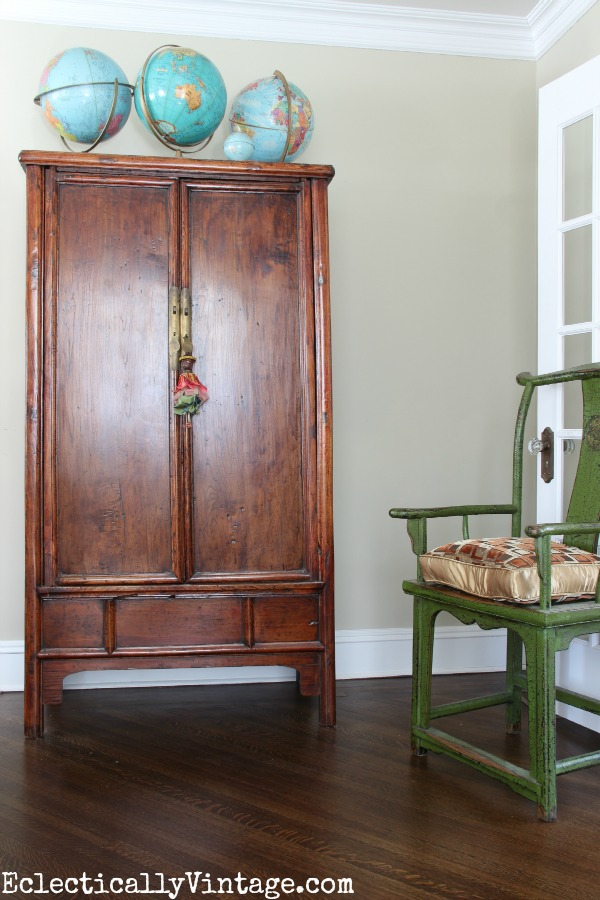 Asian armoire with globe collection - tour this eclectic living room eclecticallyvintage.com