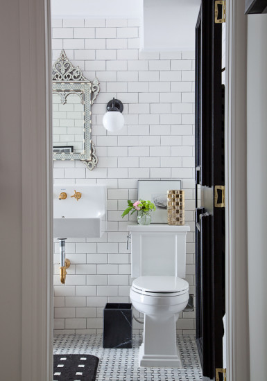 Beautiful bathroom with classic subway tile - love the mirror and brass fixtures kellyelko.com