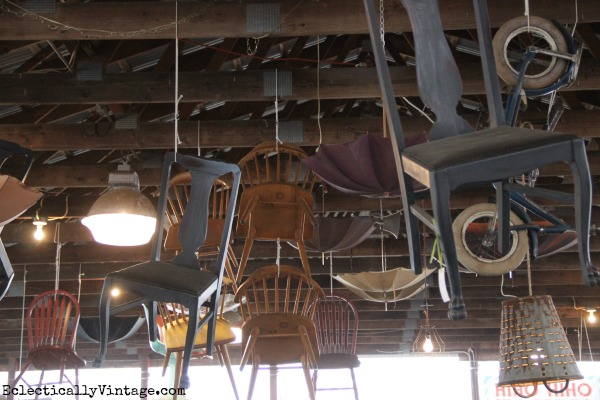 Vintage chairs hanging from the ceiling - what a cute display! kellyelko.com