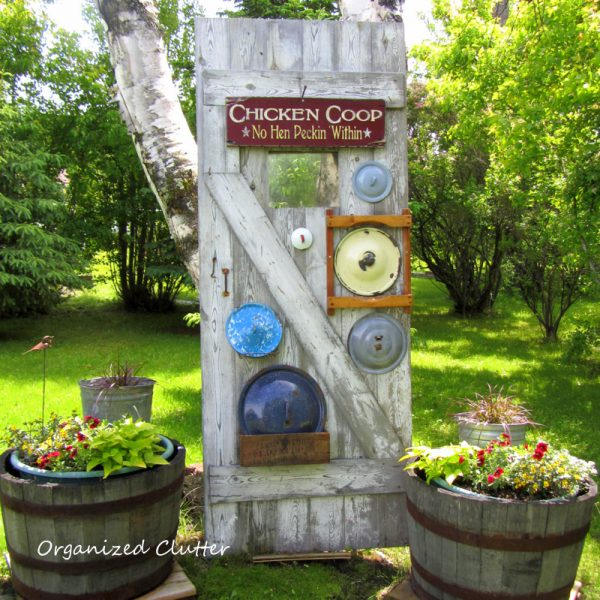 Old door with a vintage pot lid collection - love this garden! kellyelko.com