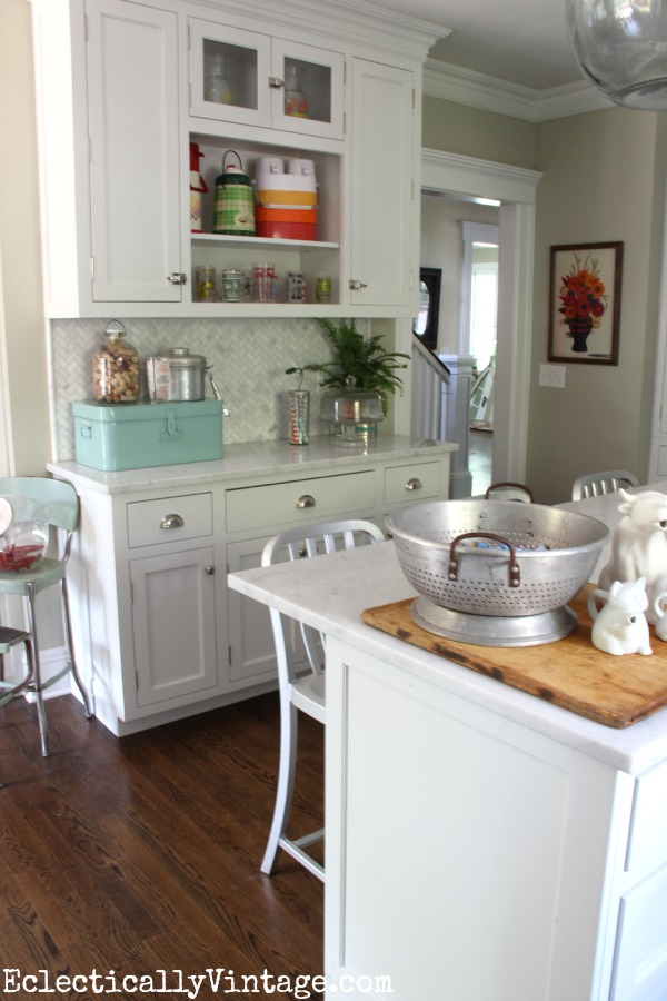 White farmhouse kitchen decked out for summer - love the colorful thermos and barware collections eclecticallyvintage.com