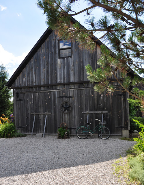 Beautiful weathered barn in this whimsical garden kellyelko.com