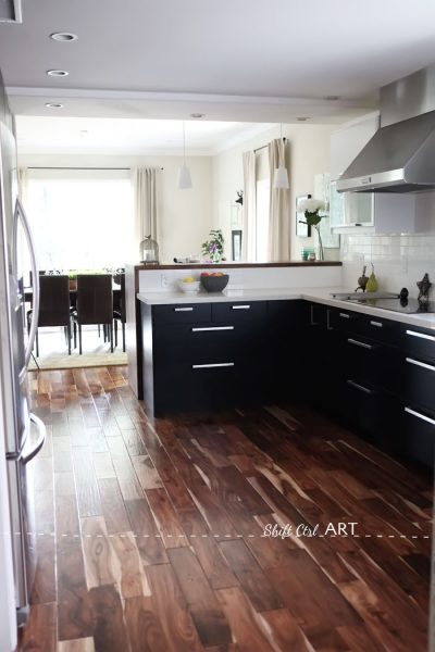 The acacia hardwood flooring is gorgeous in this Ikea kitchen remodel kellyelko.com