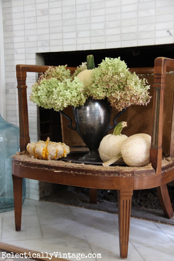 Turn an old chair into a fireplace screen - love the trophy filled with pumpkins and hydrangeas kellyelko.com