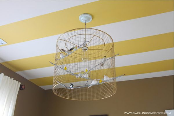 Fun striped ceiling and birdcage chandelier in this nursery kellyelko.com