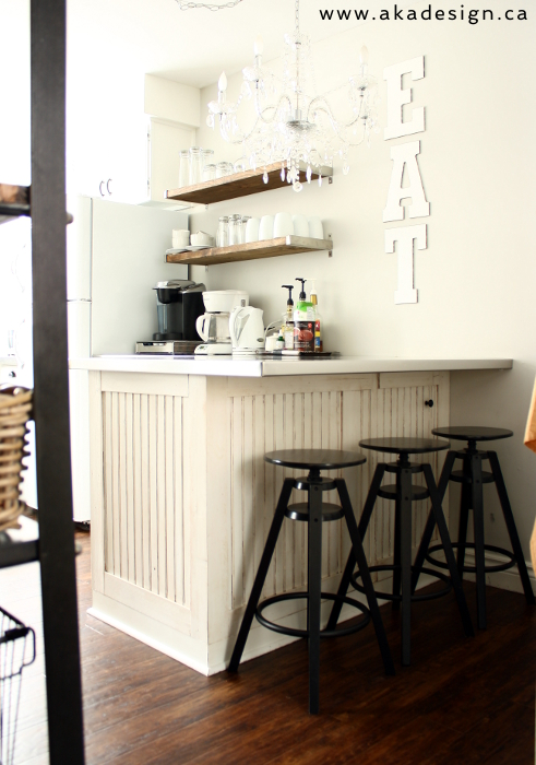Breakfast bar in this small kitchen - love the EAT sign and open shelves kellyelko.com