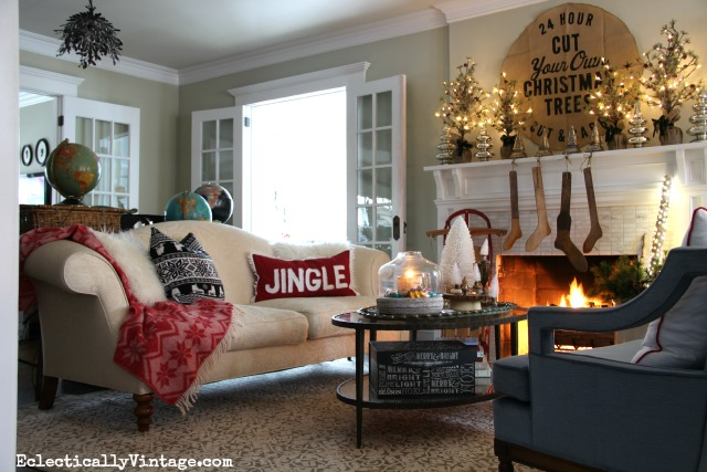 Cozy Christmas living room - love the throw and pillows and that gorgeous glowing mantel kellyelko.com