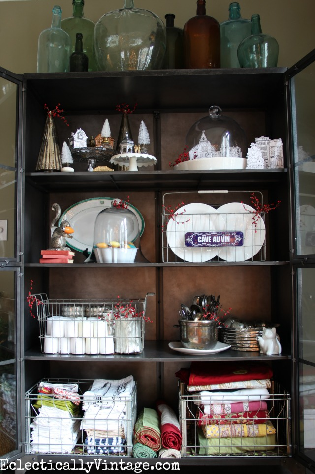 Love the collection of demijohns and this huge industrial cabinet filled with Christmas display ideas kellyelko.com