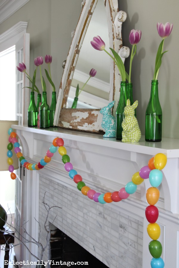 Easter mantel - love the green glass bottles, tulips and that cute egg garland! kellyelko.com