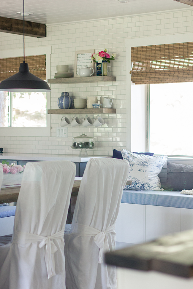 I am in love with this kitchen - subway tile, industrial lights, open shelving - all done on a budget eclecticallyvintage.com