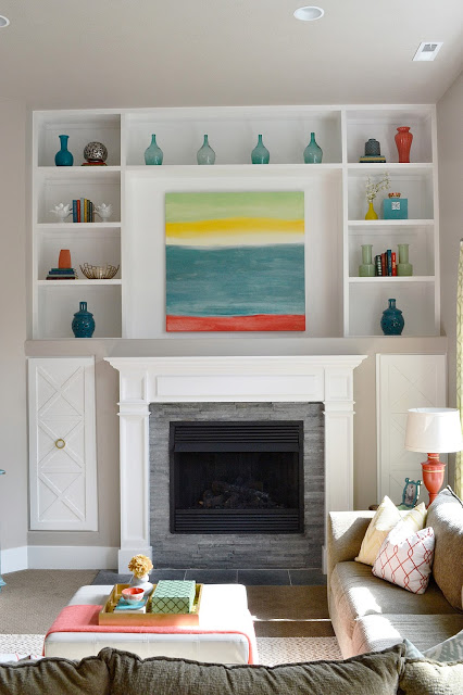 Love these built in cabinets around the fireplace and the color glass display kellyelko.com