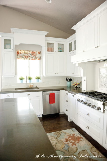 Beautiful white kitchen gets fun color from a window treatment and rug kellyelko.com