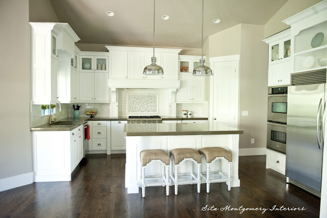 Gorgeous white kitchen - love the two pendant lights and the top glass cabinets kellyelko.com