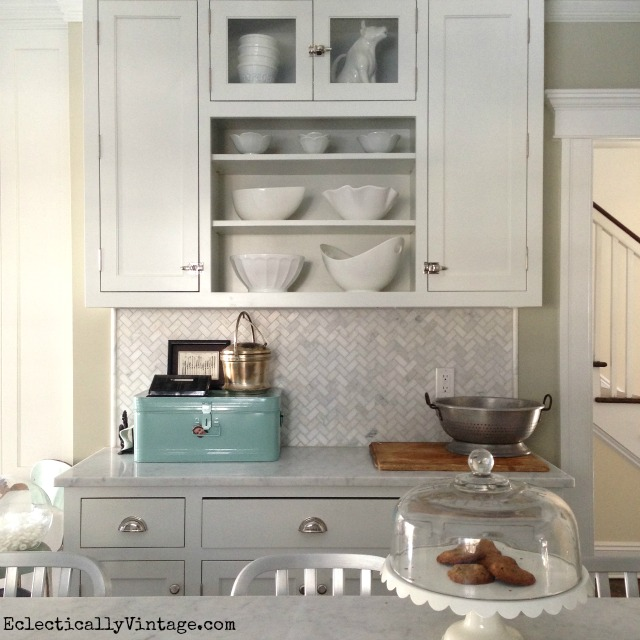 Love these open shelves filled with white kitchen accessories - and the herringbone carrara marble backsplash is gorgeous! kellyelko.com