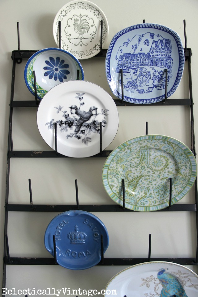 Eclectic plate wall displayed on a wall bottle drying rack! This is fabulous kellyelko.com