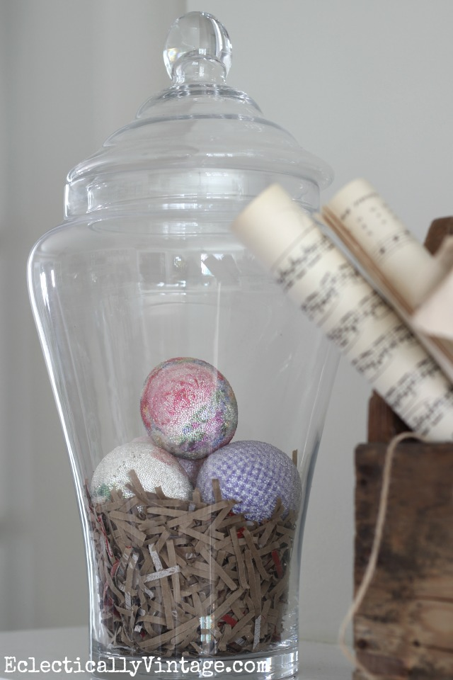 Apothecary jars are perfect for seasonal decorating - love it filled with shredded paper and eggs on this spring mantel kellyelko.com