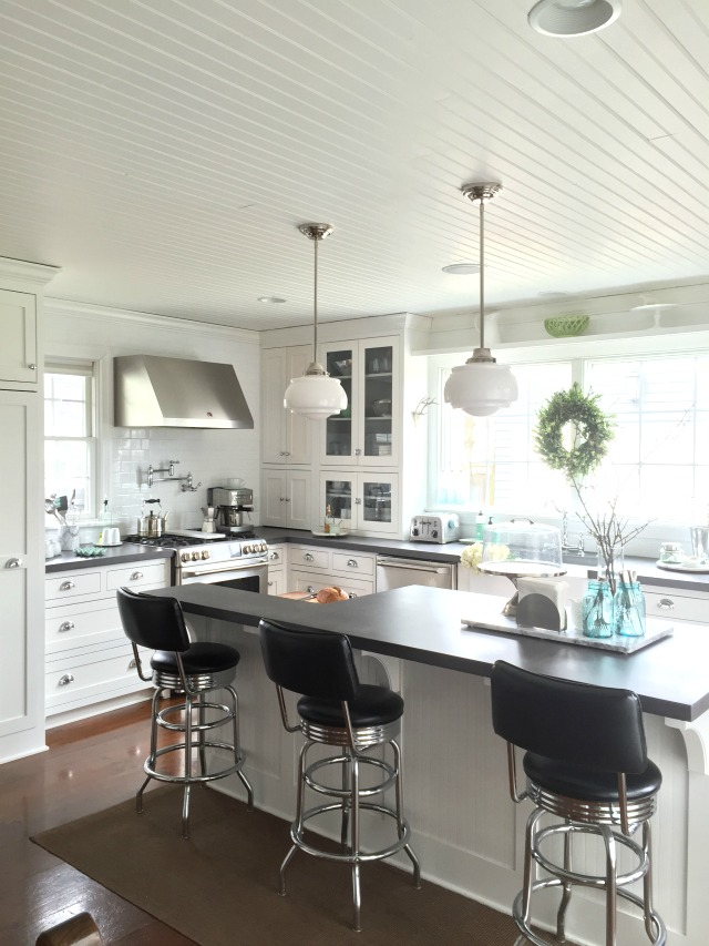 This white kitchen has such great details - the bead board ceiling, the school house lights ... kellyelko.com