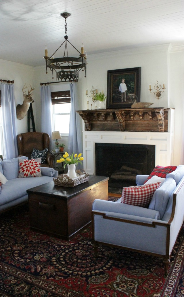Cozy cottage living room - love the rustic mantel and matching blue sofas kellyelko.com