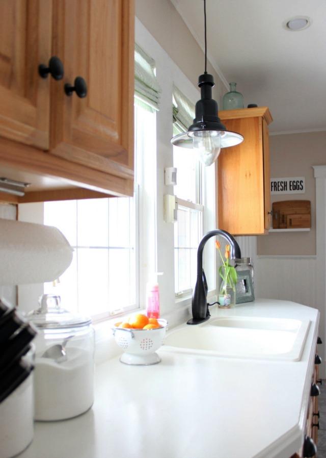 Love the industrial pendant light over the kitchen sink kellyelko.com
