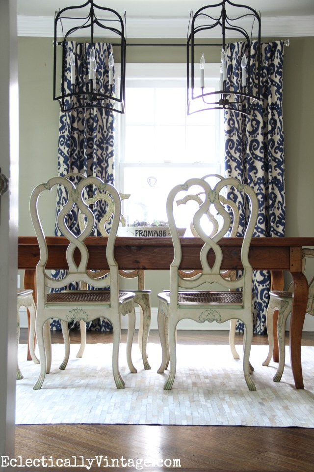 Love the drama of the double lanterns, beautiful drapes, cowhide rug and mismatched furniture in this gorgeous dining room  kellyelko.com