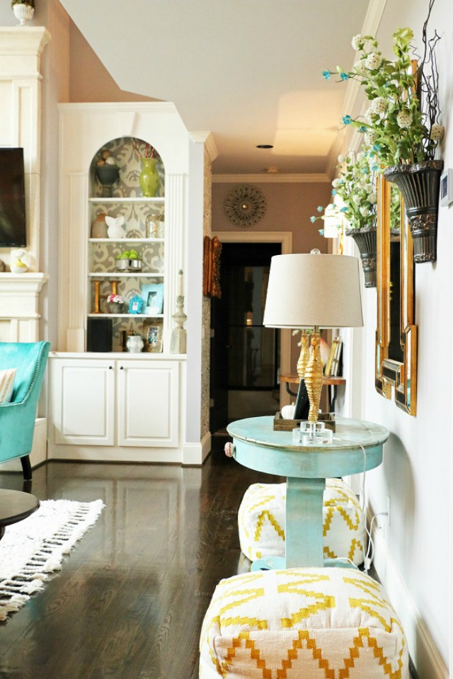 Love the painted cabinet backs and the fun yellow poufs kellyelko.com