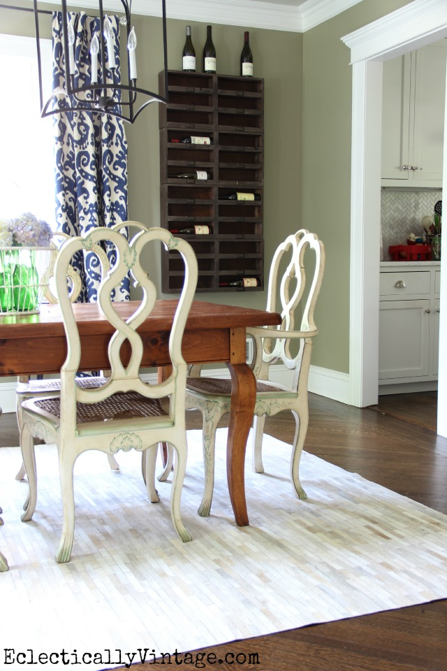 Love this eclectic dining room with cowhide rug, wine cubbies and mix of farmhouse furniture eclecticallyvintage.com