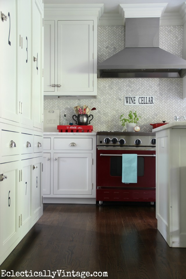Love everything about this white kitchen - the marble herringbone tile, the red stove, the wine cellar sign ... eclecticallyvintage.com