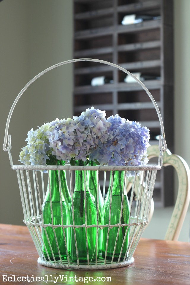 Beautiful hydrangea centerpiece in a collection of old glass bottles in a wire basket kellyelko.com