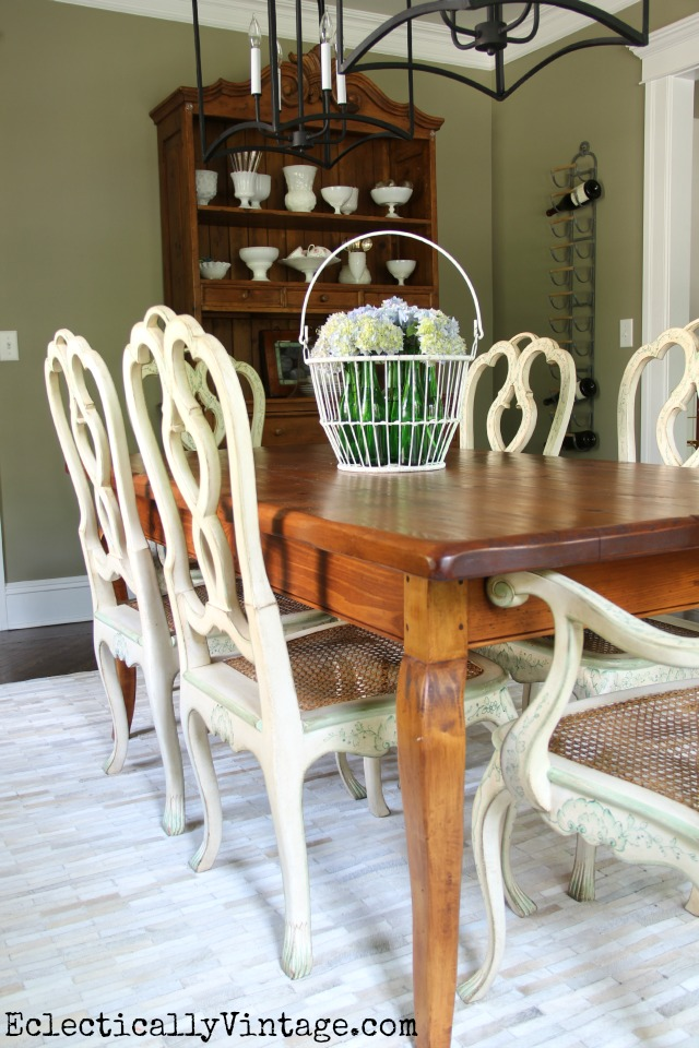 Love this rustic farmhouse table, french country chairs, cowhide rug, double chandeliers and more in this eclectic dining room kellyelko.com