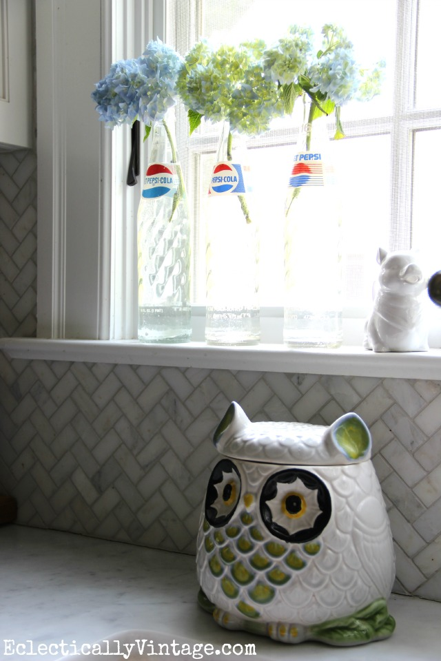 Love this kitchen window with the vintage Pepsi bottle vases and the owl cookie jar kellyelko.com
