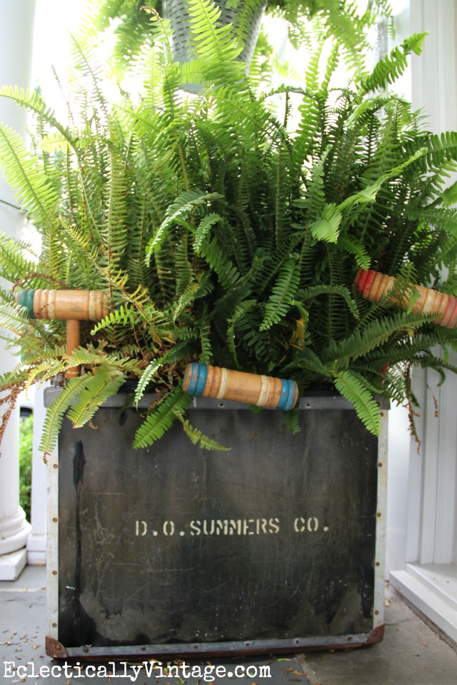 Huge old metal tub filled with ferns on this summer front porch - love the old croquet mallets peeking out kellyelko.com