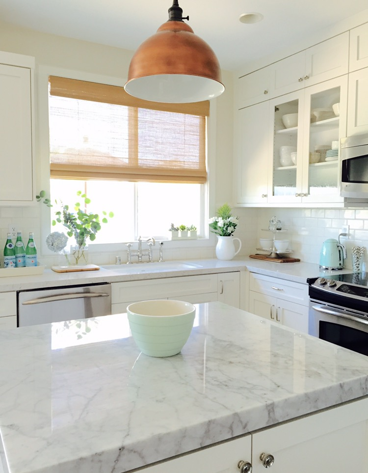Love this white farmhouse kitchen and that brass light kellyelko.com