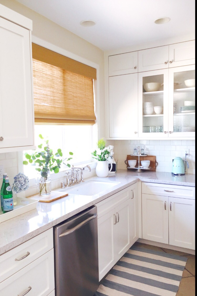 Cozy cottage home tour - love the white kitchen and glass front cabinets kellyelko.com