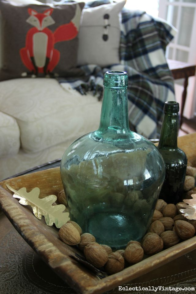 Love this dough bowl centerpiece filled with old bottles and walnuts kellyelko.com