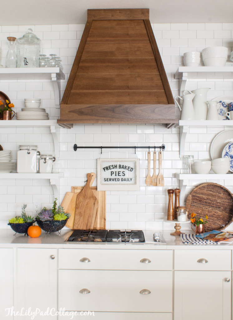 Beautiful white kitchen with wood range hood and open shelves