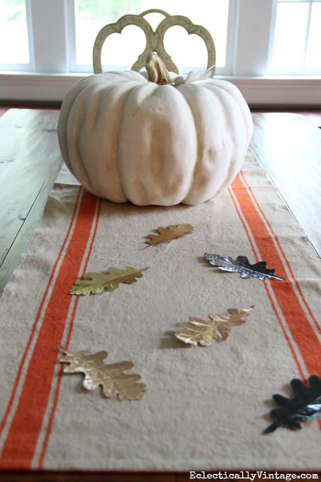 Love this fall centerpiece - a huge pumpkin, orange stripe table runner and DIY metal leaves kellyelko.com