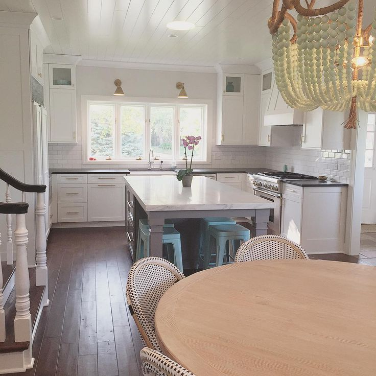 Beautiful white kitchen - love the brass sconces and beaded chandelier kellyelko.com