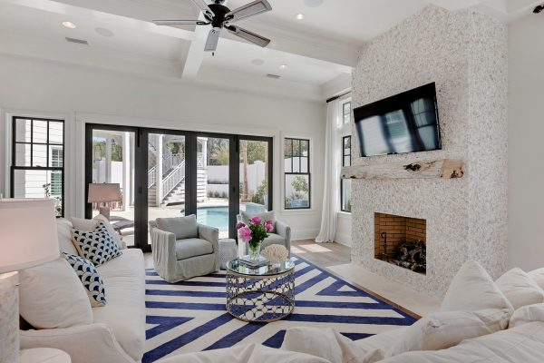 Coastal family room with fun touches like the rustic wood mantel and the shell and stucco fireplace surround - take the coastal home tour kellyelko.com
