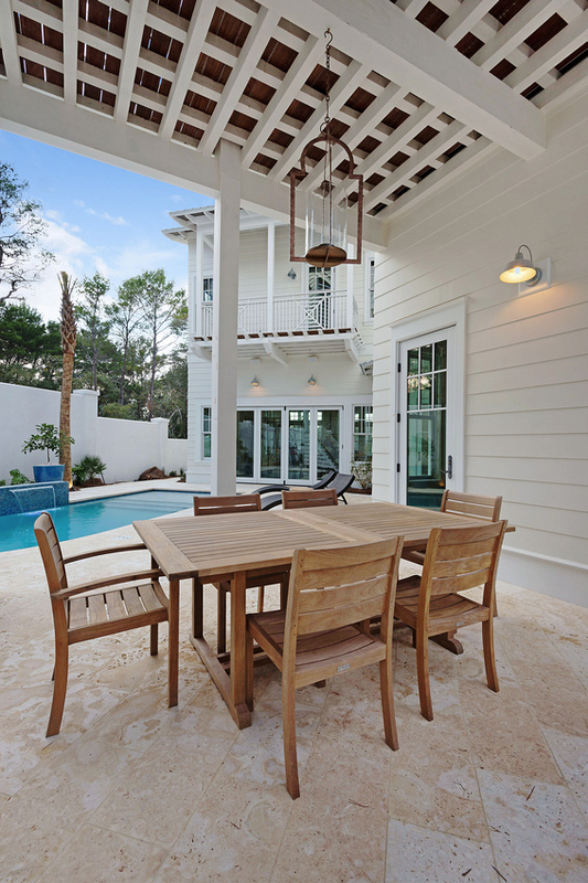 Teak outdoor dining set under a covered patio - love the outdoor chandelier - part of this beautiful coastal home tour kellyelko.com