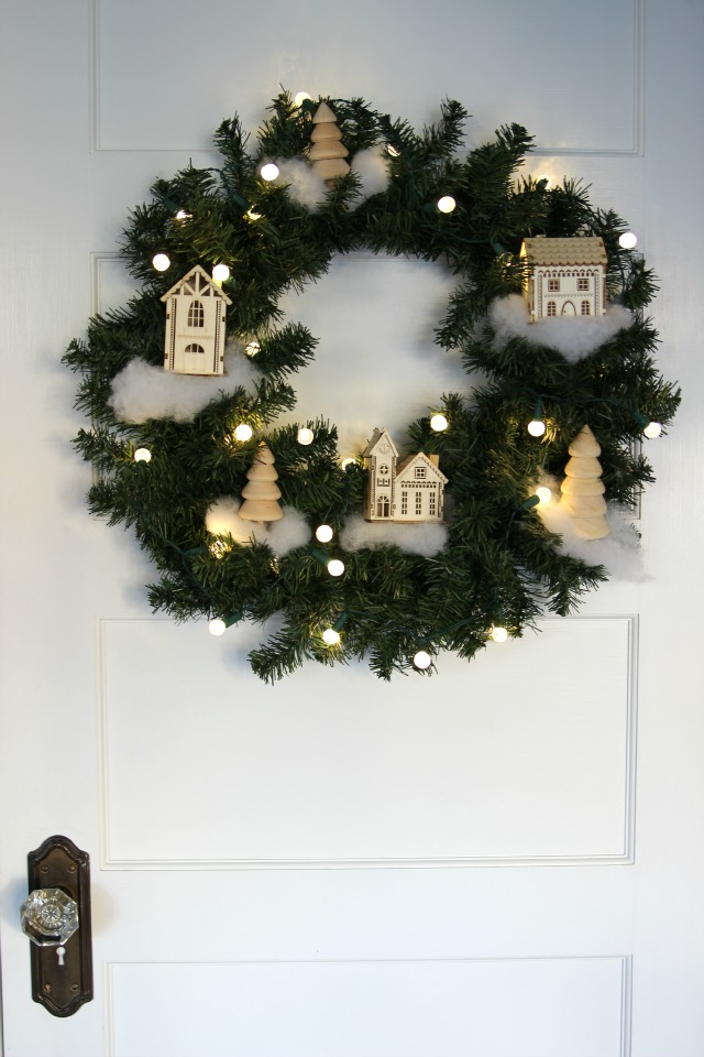 See how to make this Winter Village Wreath for Christmas! Perfect to decorate or give as a gift kellyelko.com