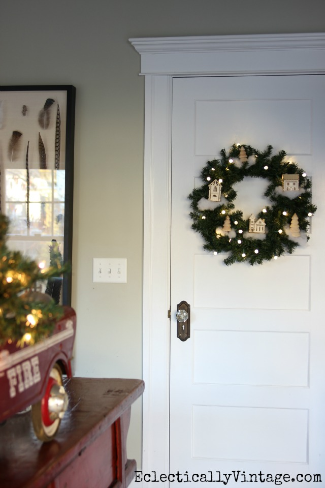 Love this festive DIY winter village wreath - the perfect Christmas decoration kellyelko.com
