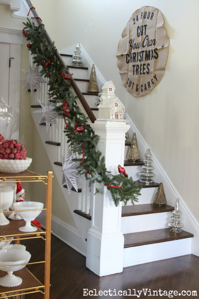Love this bannister with garland, huge paper snowflakes and mercury glass trees on each stair kellyelko.com