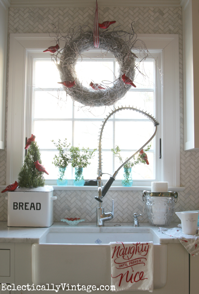 Festive Christmas kitchen window - love the white twig wreath and the cardinals kellyelko.com