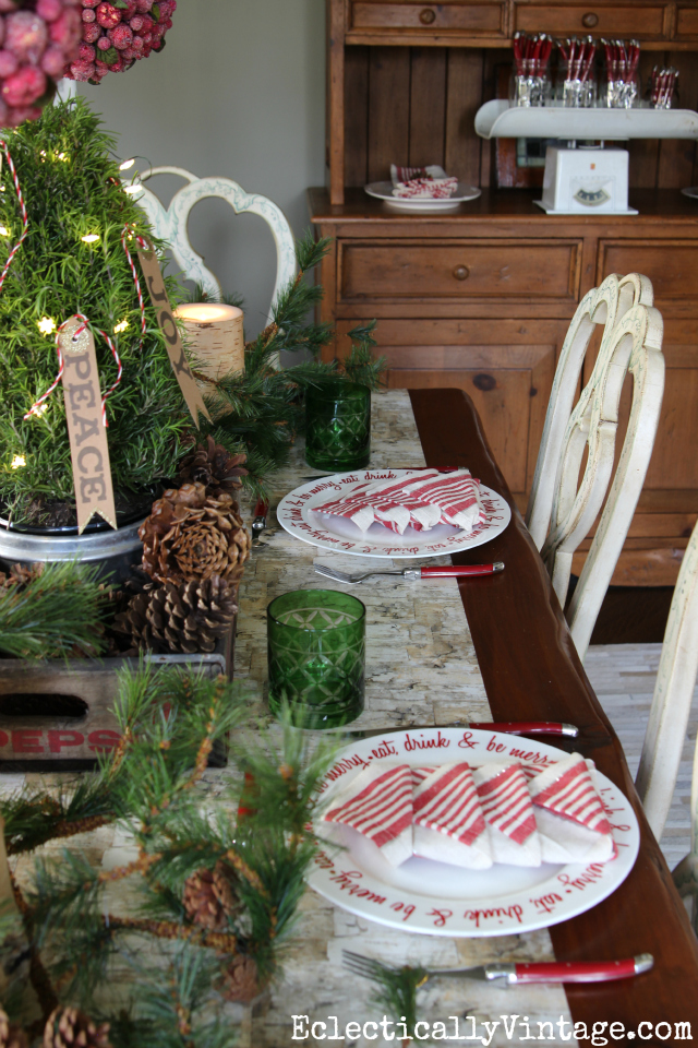 Love this festive Christmas table! The table runner is so fun and the red plates and cutlery kellyelko.com