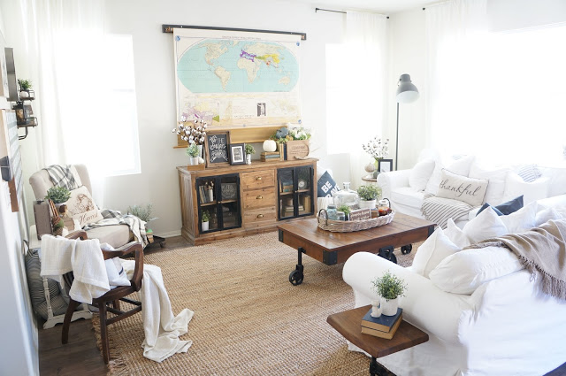 Beautiful neutral living room with map that hides the TV kellyelko.com