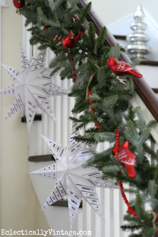 Love these huge paper stars hanging from this Christmas bannister kellyelko.com