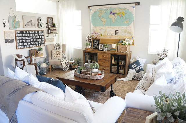 Love this cozy living room and the white slipcovered sofas. The pull down map hides the TV! ecleticallyvintage.com